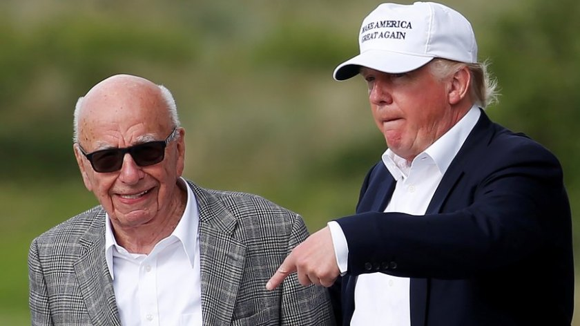 Republican presidential candidate Donald Trump speaks to media mogul Rupert Murdoch as they walk out of Trump International Golf Links in Aberdeen